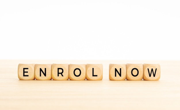 Enroll now phrase in wooden blocks on table. white background. copy space