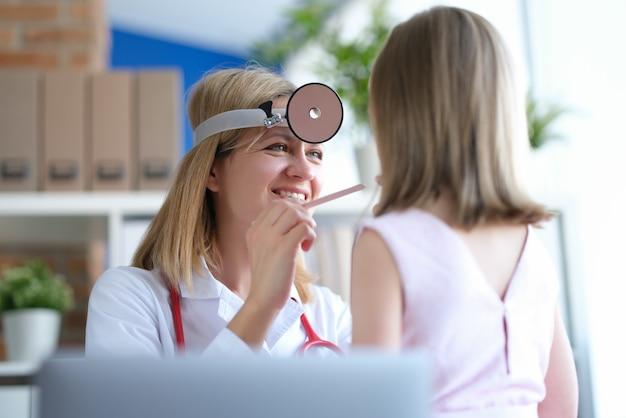 耳鼻咽喉科医が少女の喉の身体検査を行う