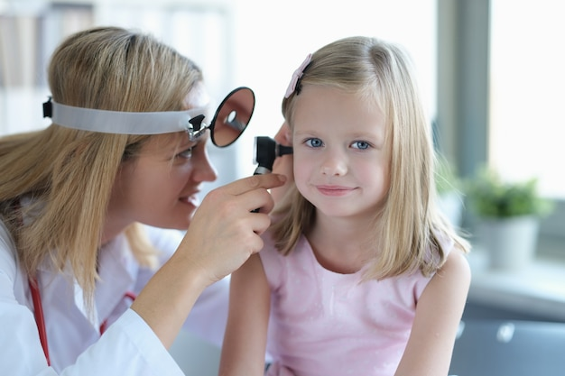 Ent doctor looks at little girls ears with otoscope closeup