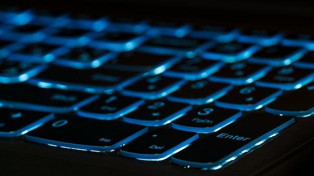 키를 입력합니다. 파란색 백라이트, 어둠 속에서 게임용 노트북 컴퓨터의 백라이트. 확대.