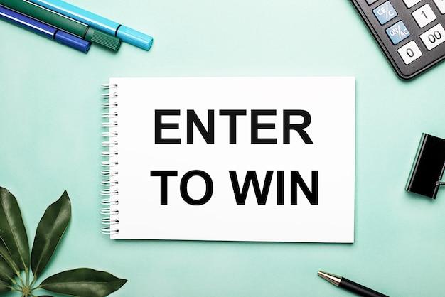 Enter to winは、文房具とシェフラーシートの近くの青い表面の白いシートに書かれています。アクションの呼び出し。動機付けの概念