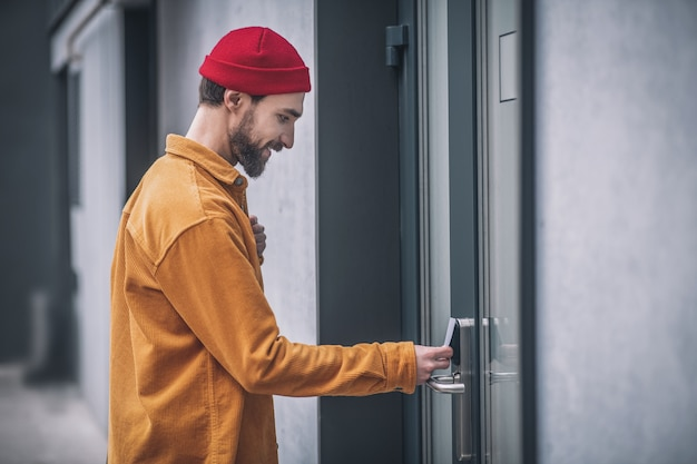 Entering the business center. bearded young man opening the door with an access card