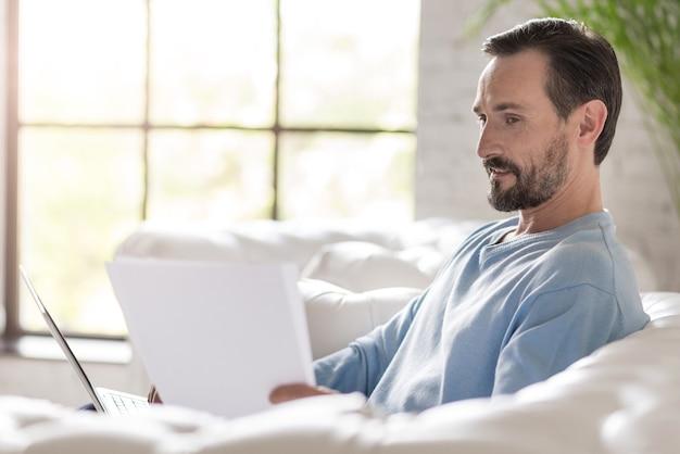 データの入力。いくつかのドキュメントを保持し、ソファに座ってラップトップで作業しているハンサムな喜んで真面目な男