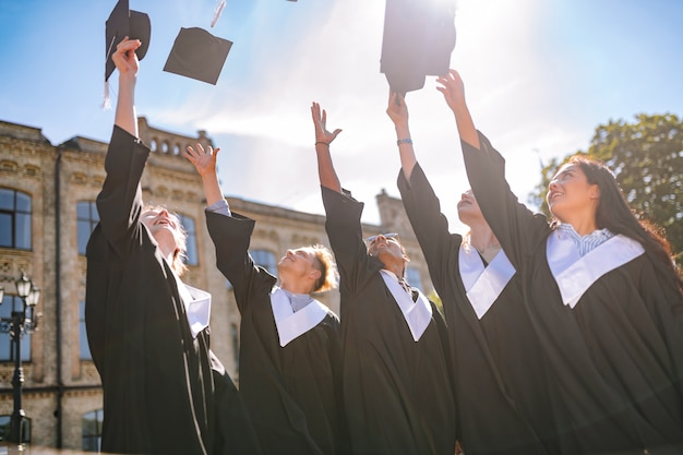 新しい世界に入る。幸せな卒業生は、大学生活に別れを告げる彼らのマスターキャップを空中に投げます。