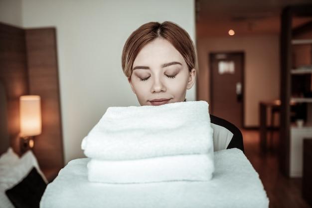 部屋に入る。クライアントのための素敵な清潔なタオルで部屋に入る若い美しいホテルのメイド