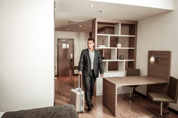 部屋に入る。荷物を持ってホテルの部屋に入る暗いスーツを着た青年実業家