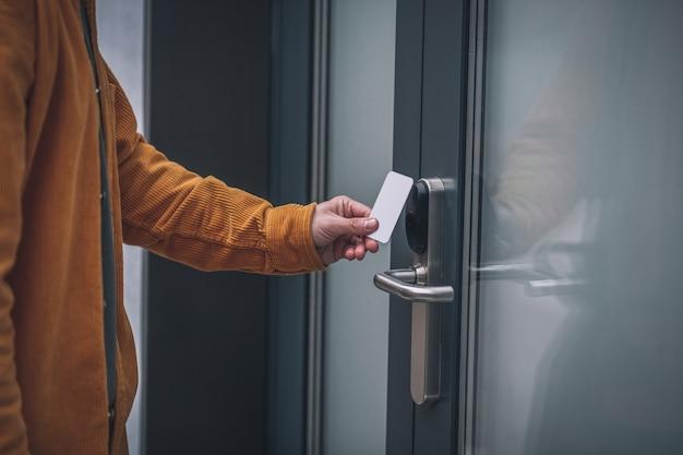 비즈니스 센터에 입장. 액세스 카드로 문을 여는 수염 된 젊은 남자