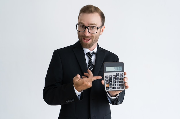 Enterprising bearded businessman pointing at calculator