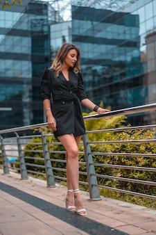 彼女がバックグラウンドで働いている黒いガラスの建物で、短いゴージャスな黒い衣装を着た進取的な金髪白人女性。右側を見て、仕事について考える手すりに寄りかかる