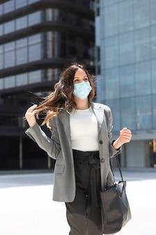 オフィスビルの近くを歩いている進取の気性のある女性。彼女は医療用マスクを着用しています。