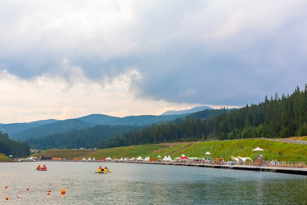 Развлечение клуба «вода» на пруду среди карпат. прокат лодок для тура по озеру.