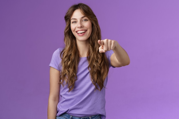 즐겁게 웃고 있는 매력적인 활기찬 소녀의 곱슬머리 헤어스타일은 행복하게 손가락을 가리키며 웃고 있는 카메라가 미소를 지으며 선택의 여지가 있음을 널리 확신하며 보라색 배경을 믿게 합니다.