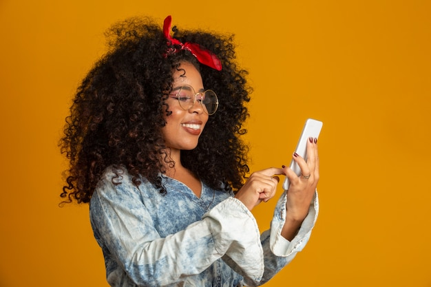 Entertained cute happy african american girl with afro hairstyle holding smartphone using device to have fun. yellow wall.