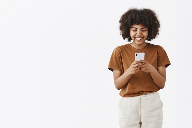 Entertained cute happy african american teenage girl with afro hairstyle in brown t-shirt holding smartphone and laughing over funny video in internet using device to have fun