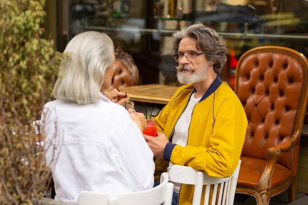 재미있는 아이디어. 수염 난 남자는 거리 카페에서 아내와 점심을 먹는 동안 깊이 생각하고 있습니다.