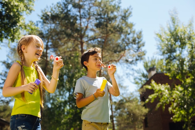 Entertaining. happy adorable kids having fun and blowing soap bubbles