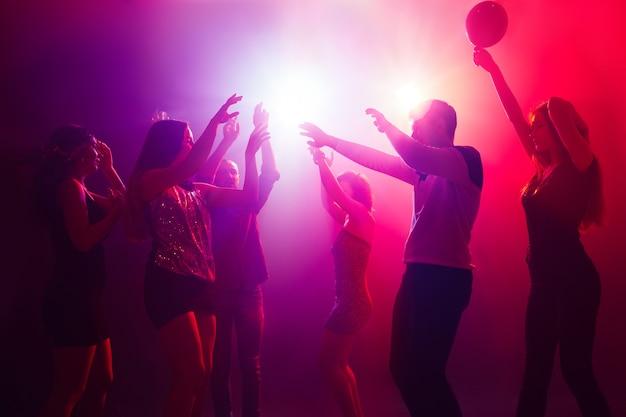 エンターテイメント。シルエットの人々の群衆は、ネオンの光の背景のダンスフロアに手を上げます。ナイトライフ、クラブ、音楽、ダンス、モーション、若者。パープルピンクの色と感動的な女の子と男の子。