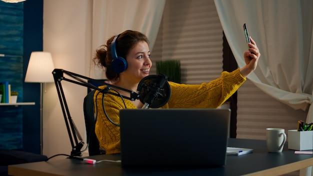ホームスタジオからの放送作業中に自分撮りをしているエンターテインメントブロガー。オンエアオンライン制作インターネットポッドキャストショーホストストリーミングライブコンテンツ、デジタルソーシャルメディア通信の記録