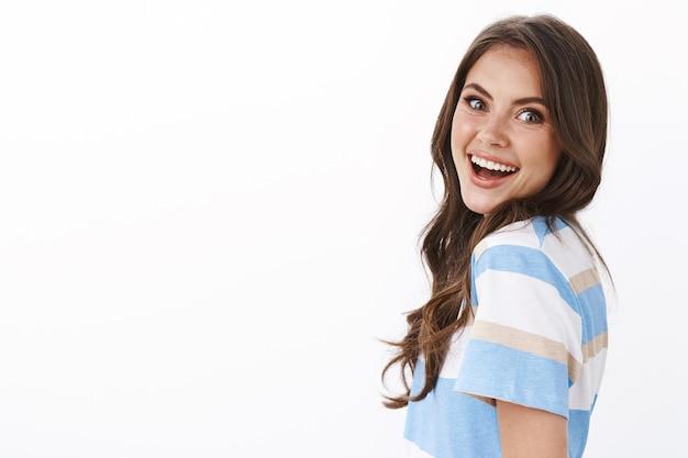 Энтузиазм: современная гламурная милая женщина, стоящая в профиль, удивленная и довольная поворачивающая камеру, восхищенная улыбка, удивленная потрясающими новостями, взволнованная и веселая