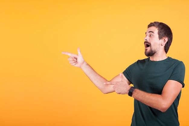 あなたのテキスト、プロモーションまたは広告のために利用可能なコピースペースを指している熱意と表現力豊かな男。男性は驚いて幸せです。オレンジ色の背景