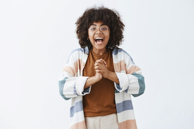 Enthusiastic active and carefree dark-skinned optimistic girl in glasses and stylish outfit clasping hands near chest and smiling broadly being excited with great news telling it to rest of people