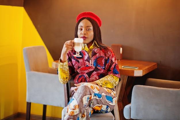 手で熱いラテのカップと居心地の良いカフェで身も凍るように赤いベレー帽とトレンディな色の服で熱狂的なアフリカ系アメリカ人女性。
