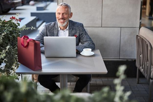 Восторженный стареющий мужчина в модном пиджаке улыбается, сидя за обеденным столом со своим ноутбуком и кофе