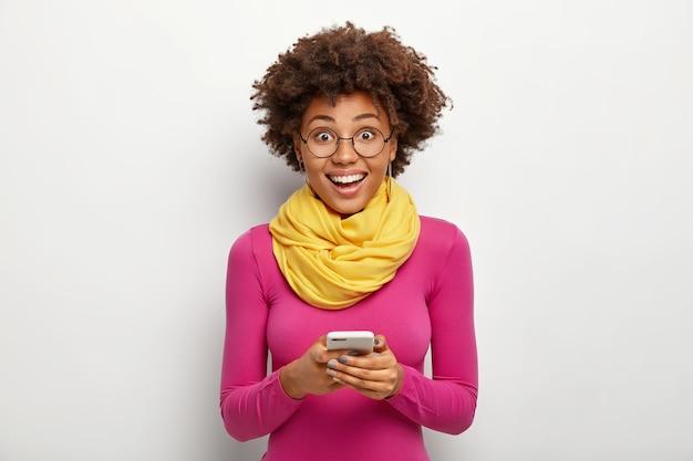 La giovane donna riccia divertita entusiastica tiene il telefono cellulare moderno, legge il messaggio di testo, indossa gli occhiali e il dolcevita rosa, pose contro il fondo bianco. concetto di tecnologia