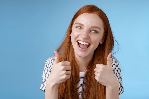 Восторженная веселая общительная рыжая красивая девушка говорит, что да, поддерживает, как отличная идея, показывает одобрение, одобряет, рекомендую жест, согласен, хороший выбор, стоит на синем фоне. копировать пространство