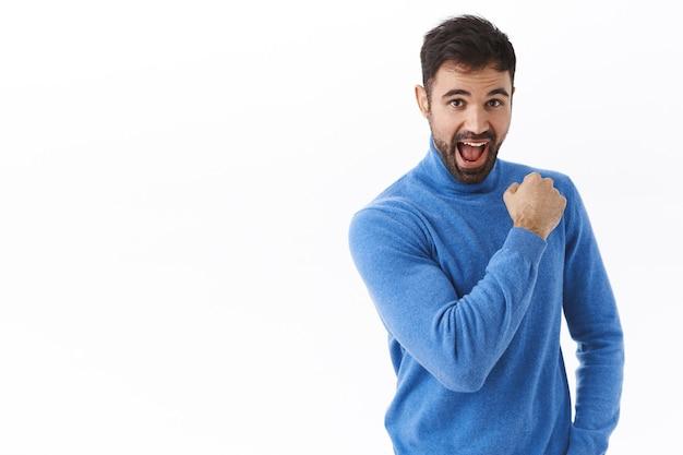 熱狂的で楽観的で、自信を持って幸せな白人の男は、続けて、ガッツポーズと笑顔を奨励し、夢に向かって行く準備ができていると感じ、成功のために服を着て、白い壁に立っています