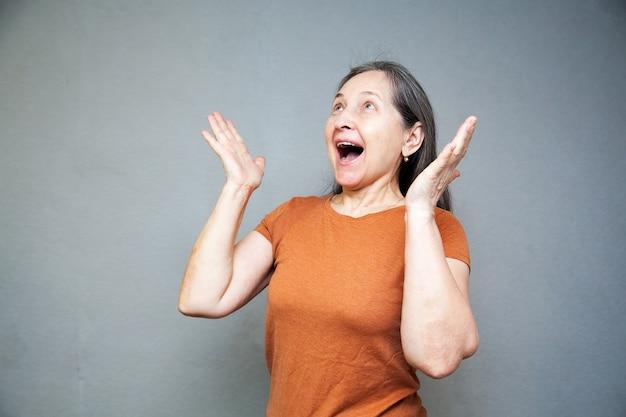 灰色の壁に茶色のtシャツで熱狂的で驚いた年配の女性