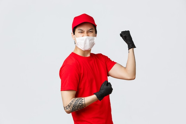 빨간 유니폼 모자와 티셔츠를 입은 열정적인 아시아 배달원, 보호용 장갑과 의료용 마스크를 착용하고 자신감을 높이고 주먹을 쥔 채 성공을 축하하고 고객에게 소포를 보낼 준비가 되어 있습니다.