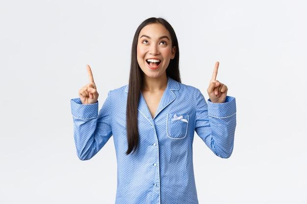 파란색 잠옷을 입은 열정적인 매력적인 아시아 소녀가 멋진 프로모션 배너 제안, 발표, 멋진 신제품에 반응하는 것을 보고 놀라며 손가락을 가리키며 웃고 있습니다.