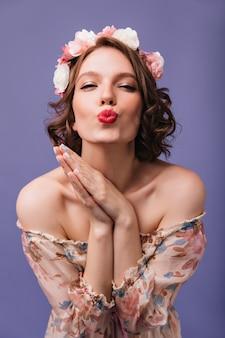 Восторженная красивая девушка с короткой прической позирует с выражением лица поцелуя. крытая фотография великолепной романтической женщины с цветами в изолированных волосах.