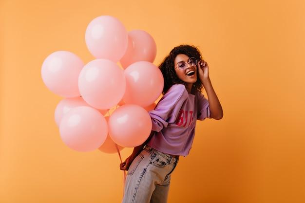 Ragazza di compleanno entusiasta in jeans alla moda rilassante alla festa. donna allegra che ride con palloncini rosa.