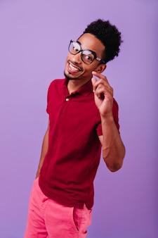 幸せな笑顔でポーズをとる熱狂的な黒人の男。トレンディなメガネでアフリカの若い男にインスピレーションを与えました。