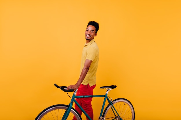 Enthusiastic black man with cheerful smile posing with bicycle. indoor photo of joyful african male model standing with bike.