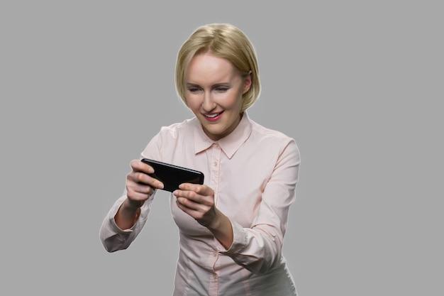 열정적 인 금발 여자는 그녀의 스마트 폰에서 재생됩니다. 게임에 몰입하는 쾌활 한 사무실 여자. 가제트 중독 개념.