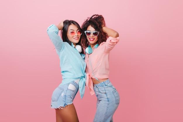 Восторженные девушки брюнетки играют с волосами, позируют, отдыхая вместе. радостная темноволосая женщина в джинсовых шортах танцует с африканским другом.