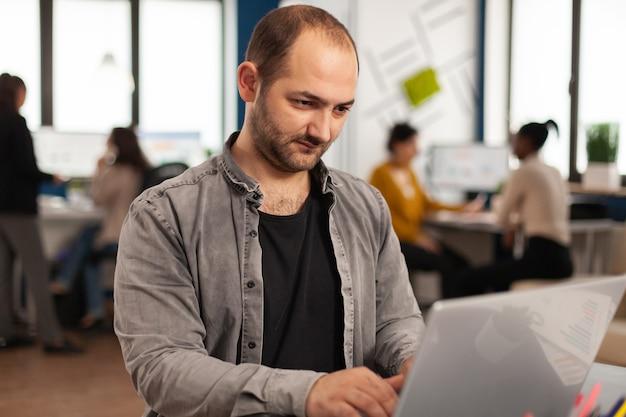 Восторженный деловой человек пишет отчет, сидя за столом в современном офисе запуска бизнеса, отправляя письма, набирая на ноутбуке, приветствуя коллегу