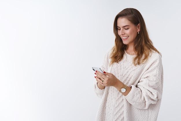 스마트폰을 사용하는 열성적인 근심 없는 매력적인 현대 여성은 온라인 소셜 네트워크에서 즐거운 대화를 나누며 웃으면서 재미있는 기사 인터넷을 읽는 즐거운 전화 디스플레이를 보고 있습니다.