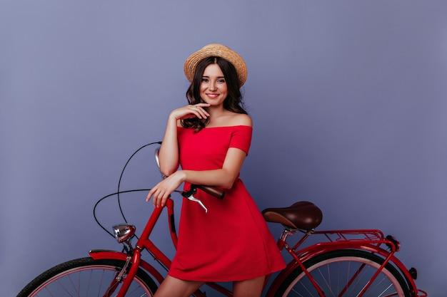 喜んで笑顔で自転車の近くに立っている熱狂的な白人の女の子。紫色の壁で写真撮影を楽しんでいるゴージャスな茶色の髪の女性の屋内写真。