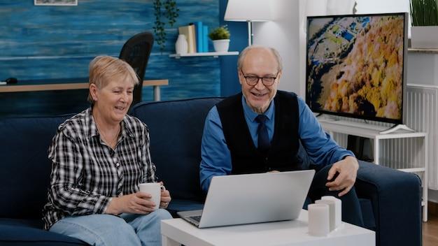 オンライン会議中にカメラで手を振っている家族の友人とビデオ通話で話しているラップトップを使用してソファで一緒に家に座っている熱狂的な年金受給者のカップル。クォーランの接続ライフスタイルの概念