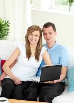Энтузиазм пара, используя ноутбук, улыбаясь на камеру