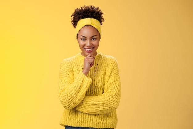 스웨터 머리띠를 하고 있는 열정적이고 멋진 흑인 젊은 여성은 만족스러운 미소를 지으며 사려깊은 카메라 메이크업 아이디어를 내고 노란색 배경에 서 있습니다.