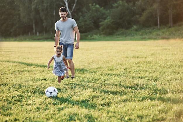 熱狂的なお父さんは娘に彼の好きなゲームをする方法を教えます。それはサッカーであり、小さな女の子でもそれをプレイすることができます。