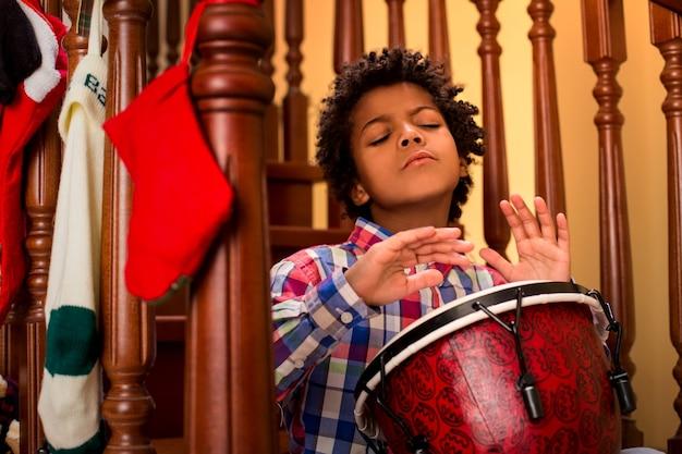 북을 치는 열정적인 검은 피부 소년 아이가 계단에서 북을 치는 그의 영감은 무한합니다 ...