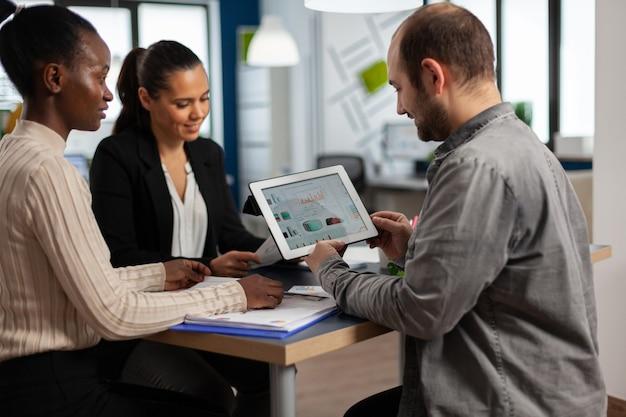 태블릿을 들고 웃고 현대 시작 비즈니스 사무실에서 테이블에 앉아 연례 재무 보고서를 읽고 열정적 인 다양한 기업인