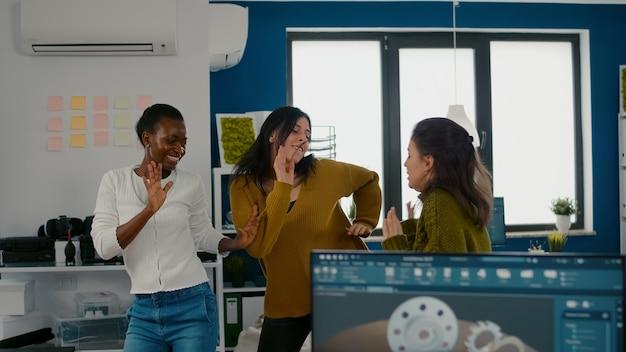 Восторженные женщины-инженеры танцуют в офисе компании, празднуя успех проекта, поют ...