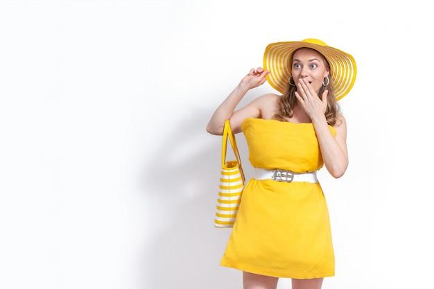 黄色の枕ドレスと白い背景の上の帽子の熱狂的な感情的な女性。夏のコンセプトです。おしゃれな少女。家の隔離を維持するための枕の挑戦。コピースペース。